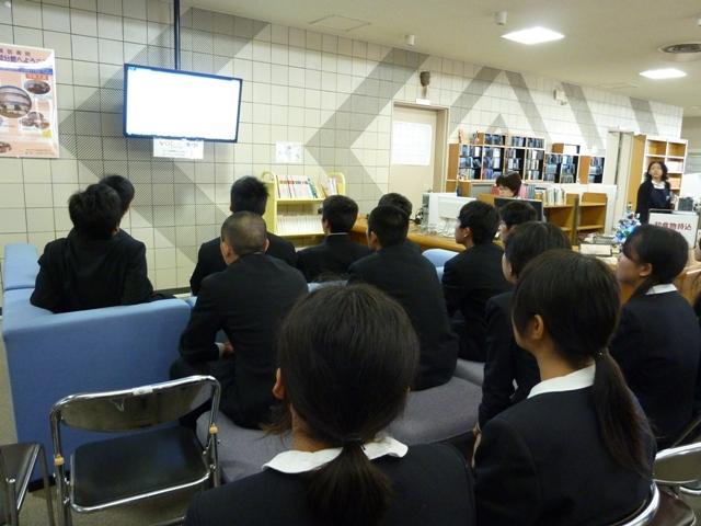 附属図書館の説明をうける生徒
